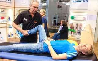 Heike Henkel (Vielfache Goldathletin) lässt sich mit Vergnügen die WaveMOTION-Behandlung demonstrieren.  | Bild mit freundlicher Genehmigung der Ludwig Artzt GmbH